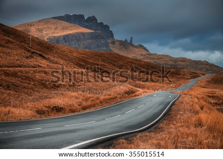 A classical vanishing point of the road on Isle of Skye, Scotland, UK, with a view over the Old Man of Storr peak - stock photo
