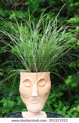 A clay head with hair from grass