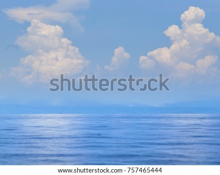A clean, fresh view of blue ocean under a blue sky with white, fluffy clouds in Thailand