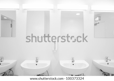 a clean new public toilet room empty - stock photo