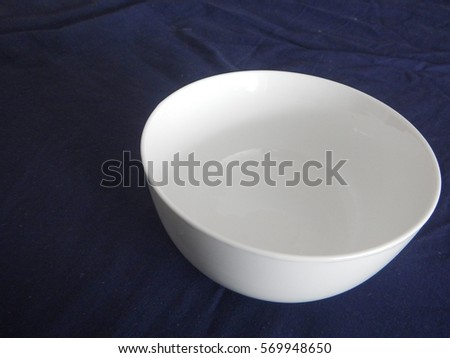 a clean white soup bowl on a dark surface