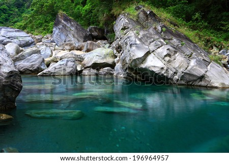 A clear, blue lake surrounded by rugged rocks.