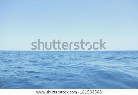 A clear blue sky over a rippled ocean. - stock photo