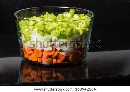 A clear bowl of fresh chopped carrots onions celery - stock photo