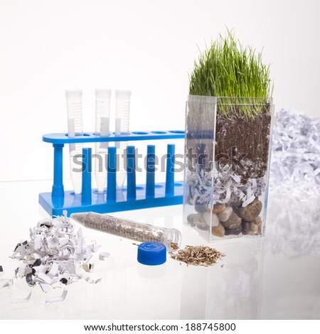 A clear container shows a cross section of pebbles, shredded paper, dirt and grass on a glass table with test tube holder, shredded paper and a tube full of grass seed. - stock photo