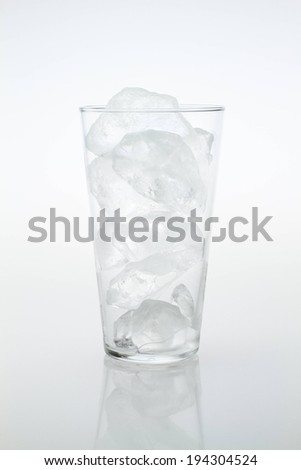 A clear glass completely filled with ice cubes. - stock photo