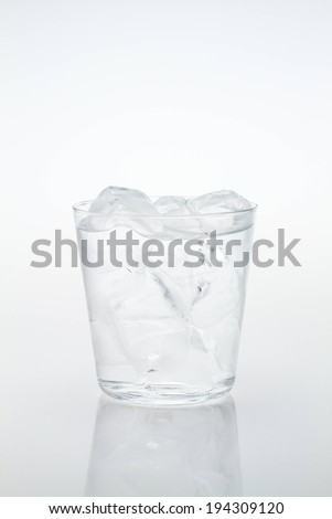 A clear glass filled with water and ice. - stock photo