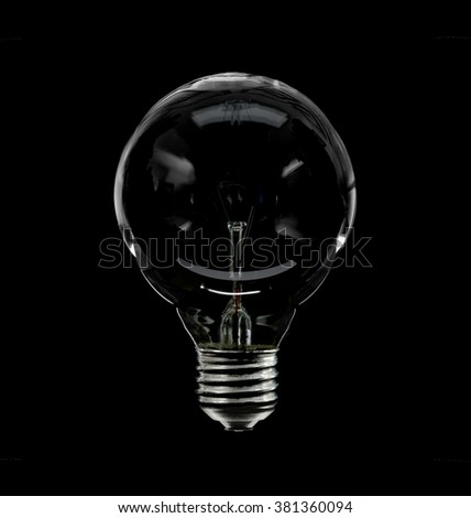 A clear glass incandescent lightbulb isolated on black - stock photo