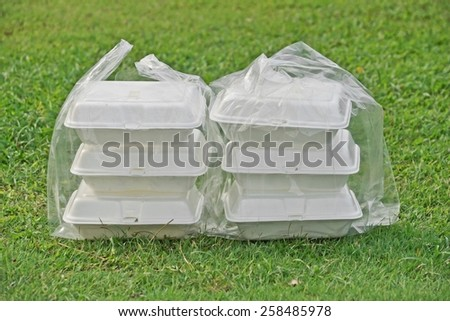 a clear plastic bags containing three foam containers on green grass background - stock photo