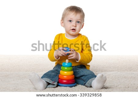 A clever infant boy is playing with a toy on the carpet - stock photo