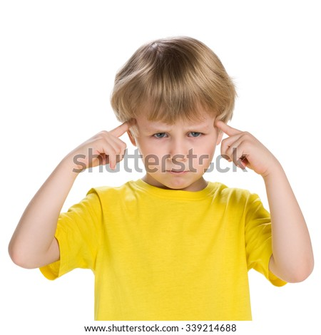 A clever little boy in a yellow shirt stands on the white background