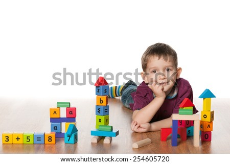 A clever little boy plays with toys on the floor - stock photo