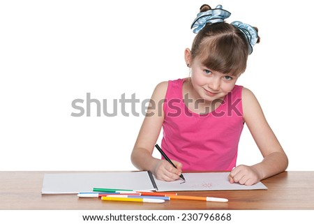 A clever schoolgirl sits at the desk and draws - stock photo