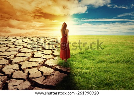 A Climate Change Concept Image. Landscape of a green grass and drought land. Woman in green dress walking through an opened field  - stock photo