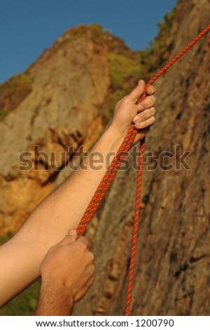 A climber belays another climber at sunset - stock photo
