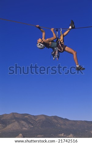 A climber dangles from her rope as she pulls her self across a tyrolean traverse. - stock photo
