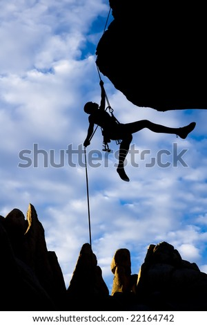 A climber dangles in midair as she rappels from the summit of a rock spire in The Sierra Nevada Mountains, California. - stock photo