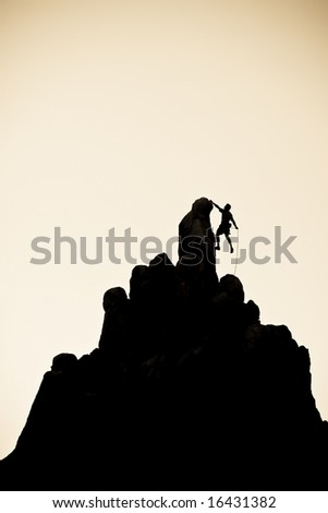 A climber is silhouetted summit-ting a rock spire in the Sierra Nevada mountains.