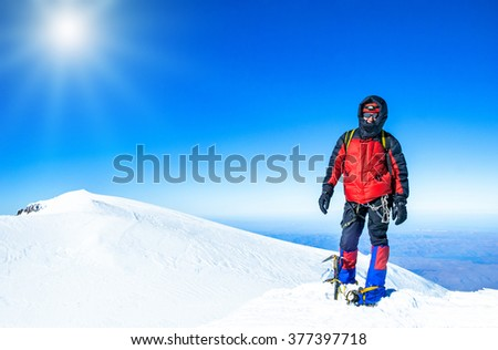 A climber reaching the summit of the mountain. Extreme sport concept - stock photo