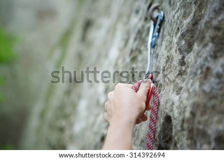 A climbers hold and quick-draw - stock photo