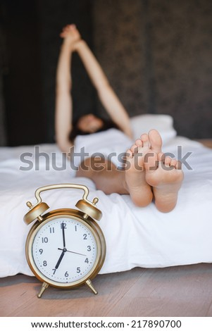A clock and the feet of a sleeping woman. Early morning.sleeping young female disturbed by alarm clock early morning on bed - stock photo