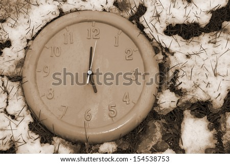 a clock face in the snow covered grass as if frozen in time in sepia