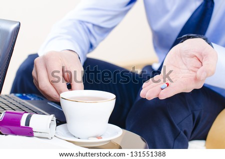 A close look to somebody taking a pill at office - stock photo