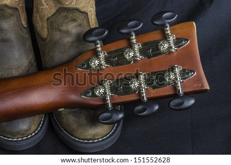 A close shot of a pair of boots and a cowboy guitar handle. - stock photo