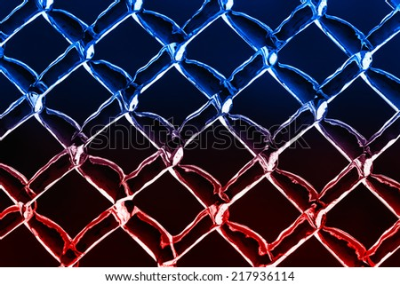 A close up abstract background image of a color inverted chain link fence.  The diamond pattern is covered in an ice texture and the image is toned in hues of cool blues fading into warm reds.  - stock photo