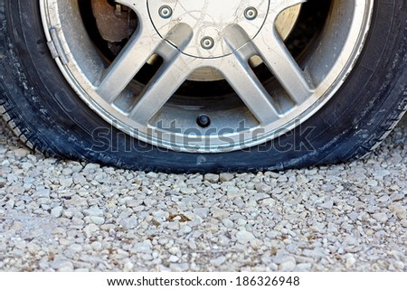 a close up, centered view of a flat car tire that has popped on a gravel road.  Room for copy-space. - stock photo