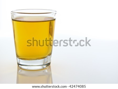 A close-up compsition of a shot glass filled with amber colored alcohol against a white background
