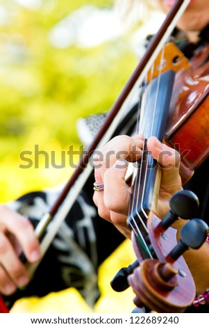 A close-up detail of a woman playing the violin at a wedding. - stock photo
