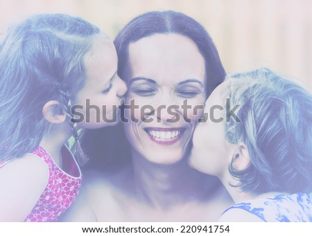 A close up family picture of two daughters on either side of their mother each giving a kiss on her cheek.  Filtered for a retro, vintage look.  - stock photo