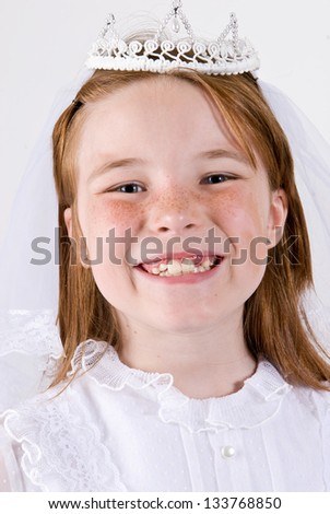 A close-up/head shot, shot straight on, of a young girl smiling in her First Communion Dress and Veil
