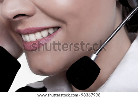 A close-up image of a beautiful woman with a friendly smile talking on a phone at a call center. Friendly service. - stock photo