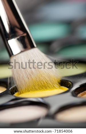 a close-up image of a eye-shadow set, with a professional makeup brush picking up some yellow color - stock photo