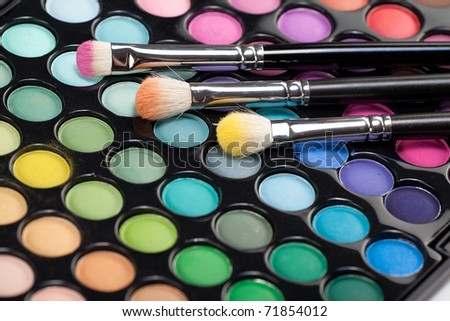 a close-up image of a eye-shadow set, with three professional makeup brushes with different pigment on them