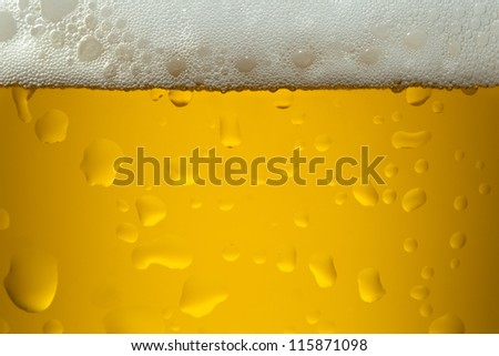 A close-up image of a yellow color beer into the glass - stock photo