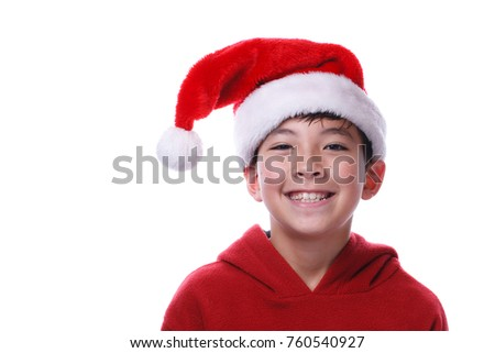 A close up image of a young boy wearing a santa hat.