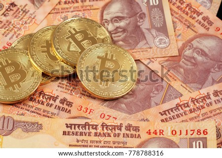 A close up image of bitcoins with Indian rupee notes