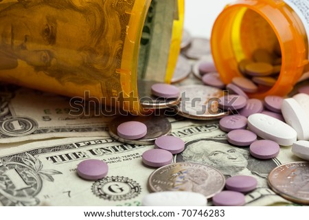 A close-up image of pills, money and prescription bottles to illustrate the cost of healthcare. / MEDICATION COSTS - stock photo