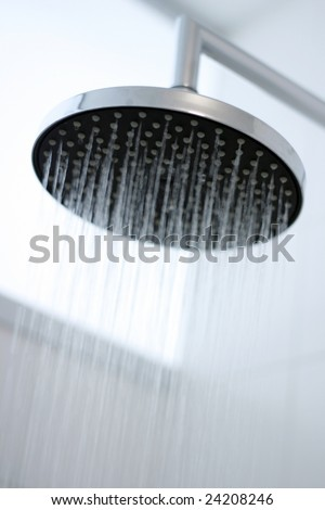 A close-up image of water running from a shower head. - stock photo