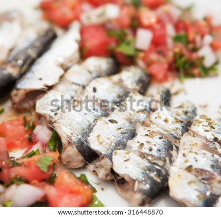 a close up in a dish with sardines baked fillet with vegetables in the blurry background (a) - stock photo