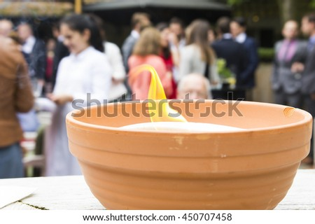 A close up of a baked clay pot with a burning flame in it. In the background there is a wedding reception going on. - stock photo