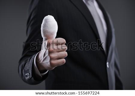 A close up of a  bandaged thumb up - stock photo