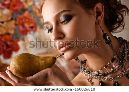 A close-up of a beautiful elegant woman holding a pear on her palm. - stock photo