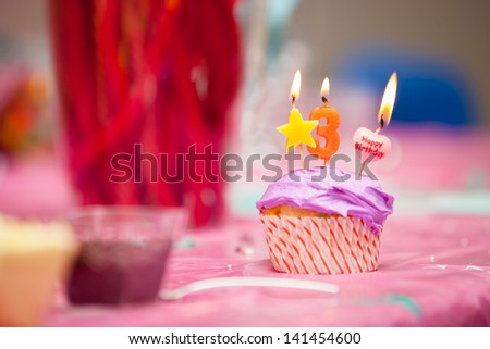 A close up of a birthday purple icing cupcake with a star, number three and a happy birthday candles all lit. - stock photo