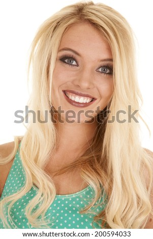 A close up of a blond woman looking with a happy expression on her face.