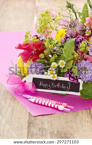 "a close up of a bouquet of flowers with a black label saying: ""Happy Birthday!"", three candles on magenta paper"