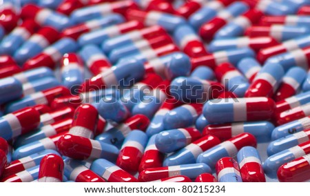 A close up of a bunch of red, gray and blue pills. - stock photo